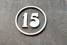 Metal number on the wall. Metal number on a grey wall Stock Photography