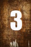 Metal numbers. Old number 3 on brown metal background Stock Image