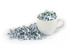 Metal nut in cup Stock Photo