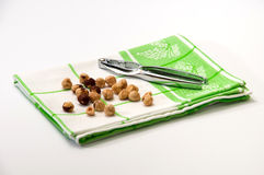 Metal nutcracker on a green rag with nuts Stock Images