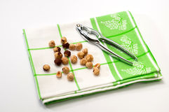 Metal nutcracker on a green rag with nuts Royalty Free Stock Image