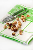 Metal nutcracker on a green rag with nuts Royalty Free Stock Images