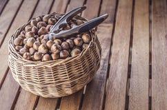 Metal Nutcracker put on the hazelnuts in the basket Stock Photo