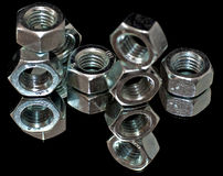 Metal Nuts. Reflected in a mirror royalty free stock photo