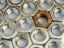Metal nuts arranged in a plane. Sidelong view from above. One old rusty nut is surrounded by many new glossy nuts Royalty Free Stock Images