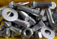 Metal nuts and bolts. Collection of metal nuts, bolts and washers in a yellow plastic bin stock photography