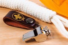 Metal o assobio, o lenço amarelo do escuteiro e a corda do escuteiro no fundo de madeira Fotos de Stock
