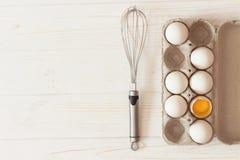 Metal o batedor de ovos e a caixa de ovos brancos crus da galinha e em w branco Imagens de Stock