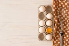 Metal o batedor de ovos na toalha e na caixa de ovos da galinha e do brancos crus fotografia de stock royalty free