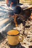 Metal o copo com café quente e o cezve no fundo da fogueira imagens de stock royalty free