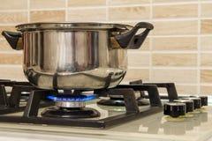 Metal o cozimento do potenciômetro que está no fogão de cozinha com flama imagem de stock royalty free