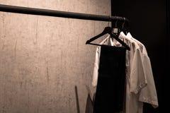 Metal odzieży poręcz z żakietów wieszakami na szarości ścianie Zdjęcia Royalty Free