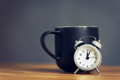 Metal old alarm clock with coffee cup Stock Photography