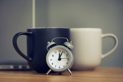 metal old alarm clock with coffee cup Royalty Free Stock Image