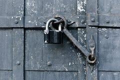 Metal old worn padlock with old door heck at the iron rusty door. Stock Images