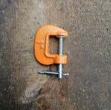 Orange clamp, small, new on wooden background royalty free stock photography