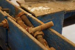 Metal oxidado velho das cabeças do parafuso na caixa azul fotografia de stock royalty free