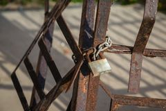 Metal Padlock and Chain attached to Rusty Railings.  Royalty Free Stock Photo