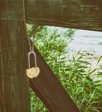 Metal padlock in the form of two hearts hanging on chain Stock Images