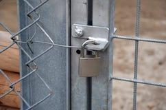 Metal padlock locking new metal gate and fence Royalty Free Stock Images
