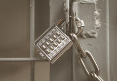 Metal padlock and pin keypad with numbers. On metal door Royalty Free Stock Photo
