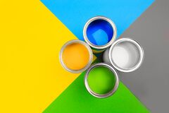 Metal paint cans and paint brushes on multicolor background. Top view. Copy space. - Image