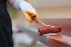 Metal painting. Worker painting  steel tube with paintroller selective focus Royalty Free Stock Photos