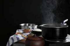 Metal pan with steam. On dark background Royalty Free Stock Images