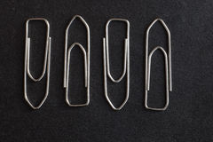Metal paper clips on a black background Stock Photos
