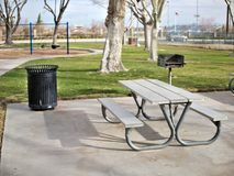 Metal park bench and picnic area in park. stock images