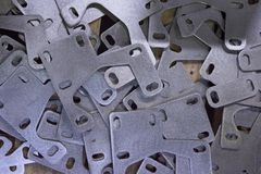 Metal parts from the bus lying in the heap.Stamping plates of complex shape, made of steel on CNC machines. stock photos