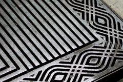 Metal patterns. Patterns in metal grate protecting trees on city sidewalk Stock Image