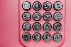 Metal payphone buttons with braille table. metallic buttons of a payphone on a red background.  stock photography