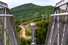 Skypark AJ Hackett Sochi, Adler, Russia - May, 2016. A metal pedestrian suspension bridge across the Mzymta River canyon in clear sunny weather against the Royalty Free Stock Images