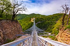 Skypark AJ Hackett Sochi, Adler, Russia - May, 2016. A metal pedestrian suspension bridge across the Mzymta River canyon in clear sunny weather against the Stock Photos