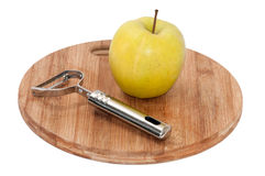 Metal peeling tool with apple on the board Stock Images