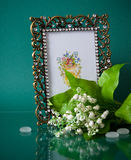 Metal photoframe and lily of the valley on green Stock Photo