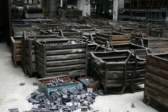 Metal pieces in factory. Large metal boxes containing metal pieces. Inside of a factory, industrial scene Royalty Free Stock Image