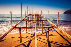 Metal pier on the beach and beautiful view to ancient fortress o Stock Images