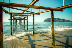 Metal pier on the beach and beautiful view to ancient fortress o Royalty Free Stock Photo