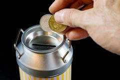 Metal piggy bank and coins. Savings and added to a metal piggy b Royalty Free Stock Photography