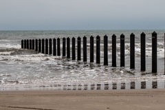 Metal pilings from shoreline into ocean Stock Image