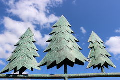 Metal pine trees against bright blue sky Stock Images