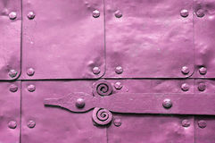 Metal pink surface of old hammered metal plates with rivets and architectural details on them. Stock Photography