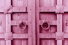 Metal pink vintage textured door with rings door handles and metal details in form of stylized flowers. Royalty Free Stock Photo
