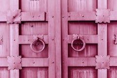 Metal pink vintage textured door with rings door handles and metal details in form of stylized flowers. Metal pink aged textured door with rings door handles Royalty Free Stock Photo
