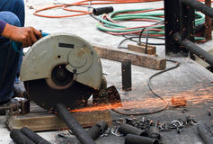 Metal pipe cutting. Worker cutting metal pipe at construction site Stock Photo