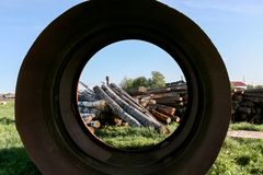 Metal pipe of large diameter, through which is visible heap of piled logs. Metal pipe of large diameter, through which is visible heap of piled logs on grass stock image