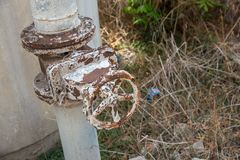 A metal pipeline valve, old weathered gas crane and pipe .Old valves have rust, Circular handle, Old valves assembled with steel p. Ipes. An old corroded rusty royalty free stock photo
