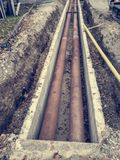 Metal pipes layed into concrete trench outdoor. royalty free stock image
